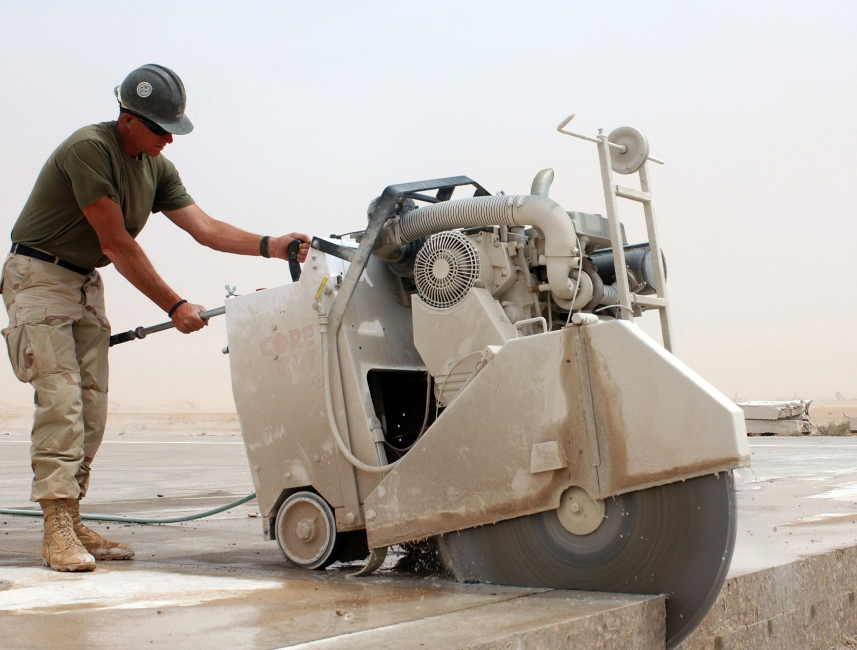 050512-N-4958O-001 Al Asad, Iraq (May 12, 2005) Ð U.S. Navy Builder 1st Class William White, assigned to Naval Mobile Construction Battalion Two Four (NMCB-24), uses a concrete saw to prepare an airfield runway expansion joint trench for repair, at the air base in Al Asad, Iraq. The Seabees of NMCB-24 are currently engaged in a massive airfield runway restoration at the airbase in Al Asad, Iraq. Two and a half miles of the baseÕs runways are being repaired, which will dramatically increase the baseÕs capability for air traffic and operations. U.S. Navy photo by Journalist 1st Class Mark H. Overstreet (RELEASED)